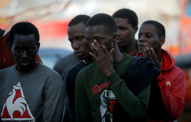 Migrants stand in a queue after arriving on a rescue boat at the port of Motril