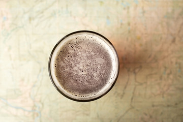 Top down view on a pint glass of beer, on a topographical map