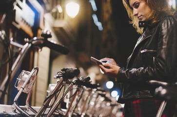 Fotomurales - Young girl in black leather jacket using in hands screen smartphone on background bokeh light in night city street, hipster biking by ecology  bicycle, lifestyle online wifi internet concept
