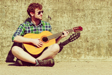 Young bearded hipster man with guitar outdoor