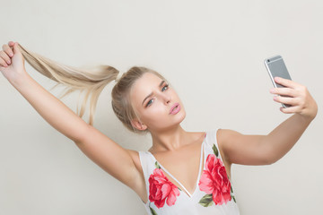 Fashionable blonde woman making selfie on mobile phone against a grey background