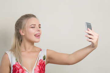 Playful blonde woman showing her tongue and making selfie on mobile phone