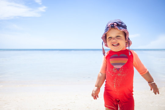 Cheerful cute happy smiling baby kid sun protective suit beach blue sea sky sunscreen background copy space