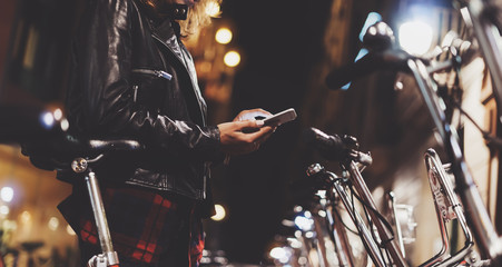 Fotomurales - Young girl in black leather jacket using in hands screen smartphone on background bokeh light in night city street, hipster biking and riding to job by bicycle, lifestyle online wifi internet concept