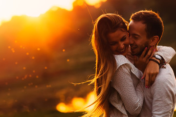 sensual hugs of a guy and his girlfriend against the background