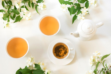 Green jasmin tea and jasmine flowers, cup of green tea on white. Top view. Teatime.