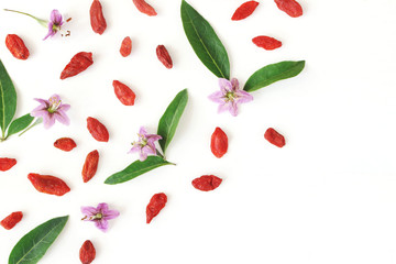 Closeup of Goji berries, Lycium barbarum. Dried Asian fruit, leaves and blossoms isolated on white wooden background. Healthy superfood. Floral pattern, decorative corner. Flatlay, top view.