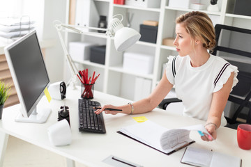 A young blonde girl is sitting at a computer desk in the office, holding a pencil in her hand and working with documents.