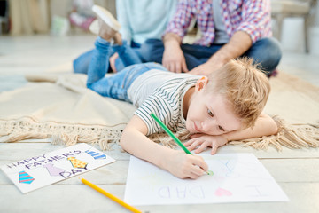 Warm toned portrait of cute little boy lying on floor in living room drawing picture for Fathers day for dad and smiling, copy space