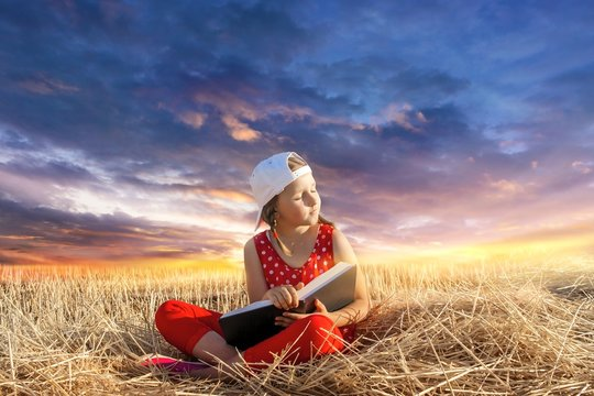 Child reading book or bible outdoors . Young Child's Hands Praying on Holy Bible .  Inner world of the child  . Relaxation in the fresh air . Portrait