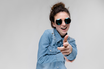 Young brunette girl in round glasses. Hairs are gathered in a bun. The girl points with her fingers.