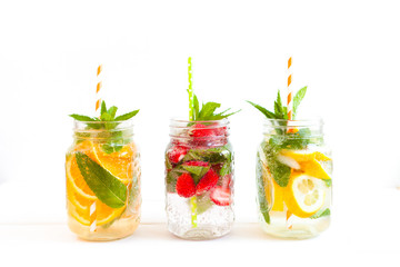 Homemade iced lemonade with mint, summer fruits and berries in a mason jar. Copy space background