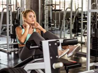 Fitness woman performing sit up on the bench