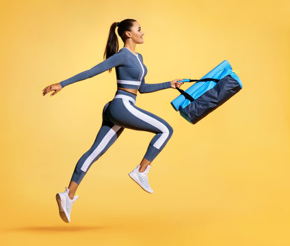 Go to training. Sporty woman with bag running in silhouette on yellow background. Dynamic movement. Side view. Sports and healthy lifestyle