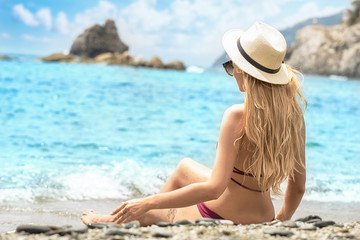 Fashion woman in summer hat relaxing on the beach.