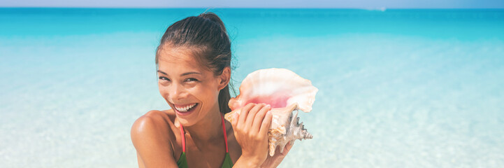 Wall Mural - Beach lifestyle vacation woman blowing a conch playing music on Caribbean holidays. Asian tourist girl smiling having fun banner panorama header crop.
