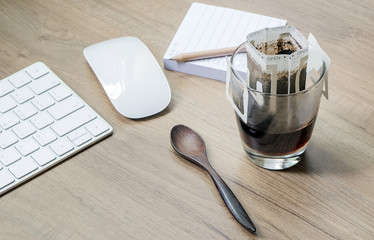 Instant freshly brewed cup of coffee or paper dripping bag on a cup on wooden table