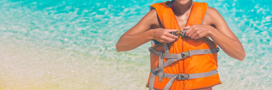 Watersport woman putting on orange life jacket for satefy on ocean activity. Panorama banner header crop. Sport lifestyle.