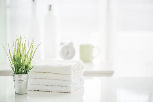 Towels on white table with copy space on blurred bathroom background