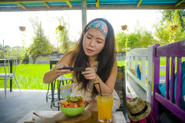young happy and pretty digital nomad Asian Chinese woman taking picture of fruit salad with mobile phone networking on internet social media