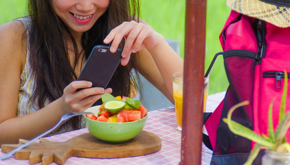 cropped face woman with mobile phone screen taking picture of fruit salad and orange juice for sharing on internet social media app in healthy nutrition