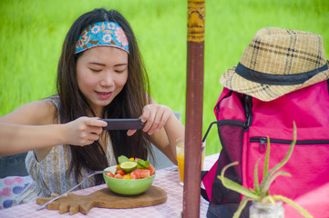 happy and pretty digital nomad Asian Chinese woman taking picture of fruit salad with mobile phone for sharing on internet social media healthy nutrition
