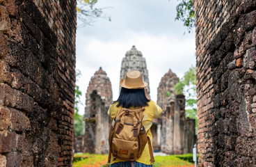 Asian tourist woman take a photo of ancient of pagoda temple thai architecture at Sukhothai,Thailand. Female traveler in casual thai cloths style visiting city concept.