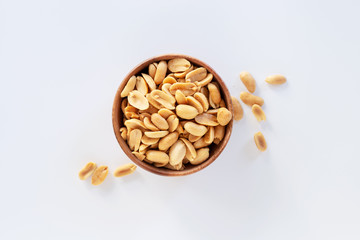 Roasted salted peanuts in wooden bowl on white background.
