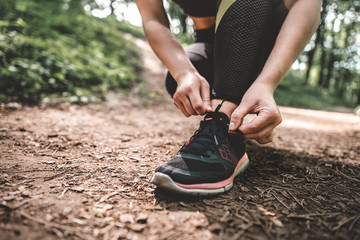 Sports woman tying shoelaces before jogging outdoors. Cropped image of young athletic woman prepares to running outdoors on the forest path. Slim girl ties up shoelaces on sneakers before in the park