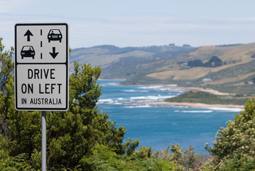 Drive on left, a caution sign along a coastal road in Australia