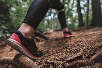 Sporty woman climbs on the forest path. Close-up of females athletic legs overcomes steep climbs on training outdoors. Young woman jogger climbing on the forest trail.