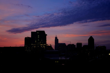 The skyline of Raleigh North Carolina backlit by the pink early morning twilight sky as viewed from Boylan Bridge