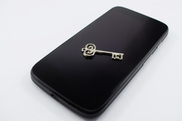 cell phone and key on it, on white background