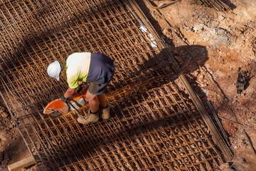 Workman cutting iron mesh, horizontal