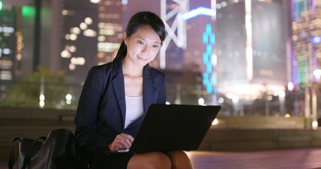 Businesswoman use of tablet computer at outdoor in the evening