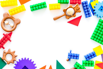 Colored construction toys for children frame on white background top view copy space