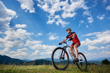 Athletic professional sportsman cyclist in sportswear and helmet cycling cross country bike in Carpathian mountains against blue sky with clouds on summer. Active lifestyle and outdoor sport concept