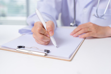 Close up on asian female doctor hands writing something on clipboard