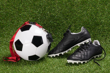 ball and shoes for football with a whistle for the referee, on the green field