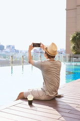 Asian man using a smartphone to take a photo of swimming pool background