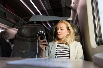 Businesswoman communicating on cellphone using headphone set while traveling by train in business class seat.