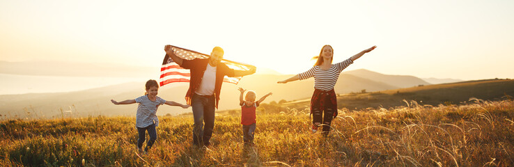 happy family with flag of america USA at sunset outdoors.