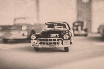 Vintage retro car. A stylized image imitating an old film photo with a faded color, vignetting, granularity.