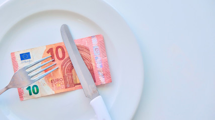 Euro banknote on a white plate, cash in Europe, the cost of lunch in the restaurant