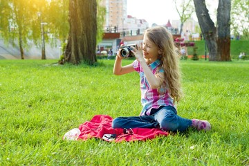 Little girl child of 8 years looking at camera sitting on green lawn in city park.
