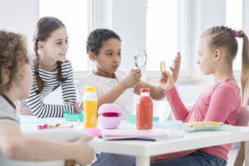 A young boy looking through a magnifying glass and a girl holding a slice of cucumber while other kids are watching during a snack break in school. Bottles of juice and lunch boxes on the table