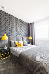 Real photo of grey bedroom interior with king-size bed, brick wall, yellow lamps and handmade knot cushion