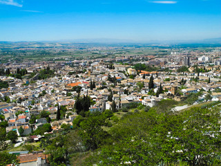 Albaicin, Old muslim quarter, white houses with orange tiling roofs, district of Granada in Spain. View from the top of Sacromonte mountain. Panorama.