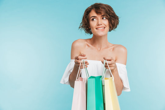 Portrait of a smiling pensive woman holding shopping bags