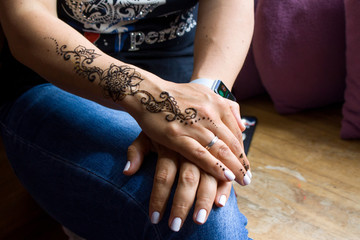 henna tattoo on women hands. Mehndi is traditional Indian decorative art. Close-up, overhead view - beauty and fashion concept